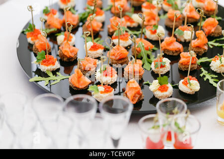 Buffet at the gala dinner. Assortment of canapes. Banquet service. catering food, snacks with salmon and caviar. rye, wheat bread. - Stock Photo