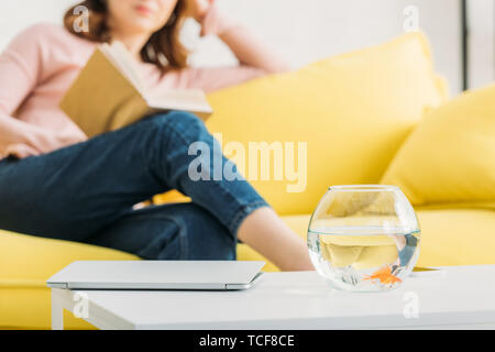 cropped view of woman resting with book on sofa near table with fish bowl - Stock Photo