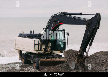 Heavy excavator working on the beach, excavator digs stones and pebbles - Stock Photo