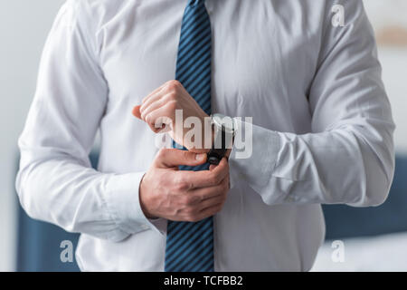cropped view of businessman in formal wear touching watch - Stock Photo