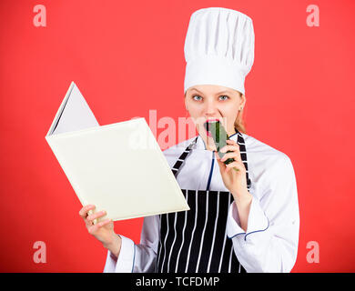 Hungry. restaurant menu. Culinary dieting. Housewife with cookery book. professional chef in kitchen eat cucumber. Cuisine. woman in cook hat and apron. happy woman cooking healthy food by recipe. - Stock Photo