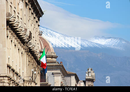 Historical building in Catania, Sicily, Italy with waving Italian flag. In the background cupola of famous Saint Agatha Cathedral and Mount Etna with snow on the very top of the volcano. - Stock Photo