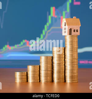 Small toy house model and coins stacks in growth graph. Planning savings money of coins to buy a home concept, mortgage and real estate investment - Stock Photo
