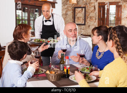Waiter in white shirt and black apron serving delicious dishes to family with child at restaurant - Stock Photo