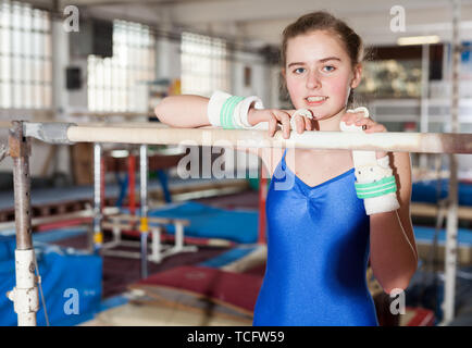 Portrait of cheerful teenage girl doing exercises on sports equipment in gym - Stock Photo