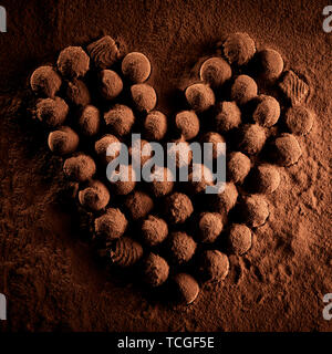 Several confectionery bonbons covered in chocolate dust lying on top of brown cocoa powder in heart shape - Stock Photo