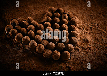 Romantic heart shaped arrangement of luxury chocolate balls, bonbons or pralines dusted with cocoa powder viewed low angle for a Valentines card - Stock Photo