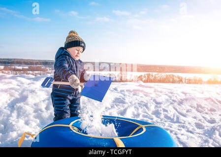 The boy pours snow child's shovel. In the winter on the street in the city of the weekend. Rest with a child in nature, tubing for skiing from a hill. - Stock Photo