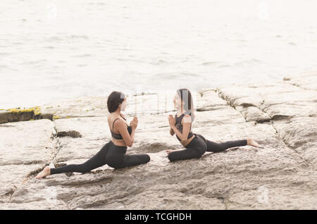 Sporty young women doing stretching. Variation Eka Pada Rajakapotasana exercise. Slim women practicing yoga outdoor on the beach, blue sky. Calm, relax, healthy concept - Stock Photo