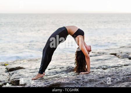young woman upward bow or wheel pose yoga pose