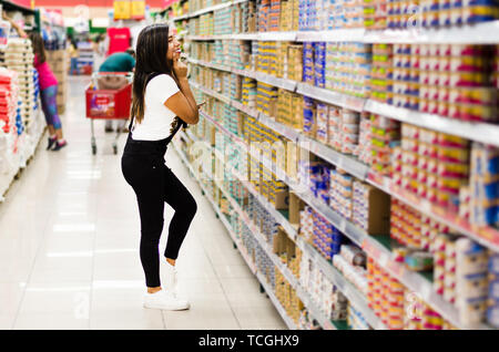 Thoughtful woman doing house shopping for pantry in supermarket - Stock Photo
