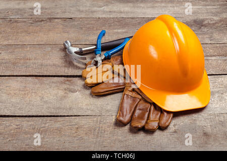 hardhat and old leather gloves - Stock Photo