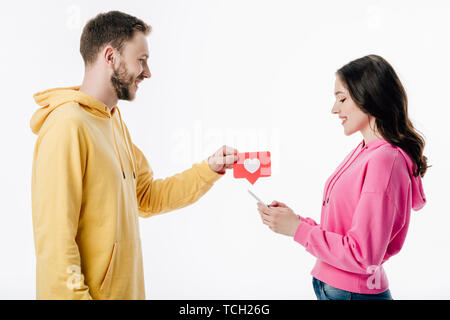 side view of smiling young man giving red paper cut card with heart symbol to girlfriend using smartphone isolated on white - Stock Photo