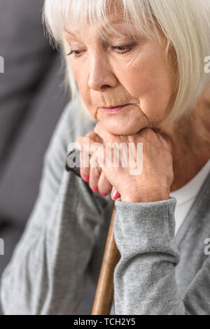 pensive senior woman holding wooden cane and looking down - Stock Photo