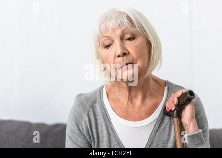 pensive senior woman with wooden cane looking down - Stock Photo