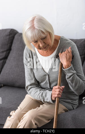 pensive senior woman with wooden cane sitting on sofa in living room - Stock Photo