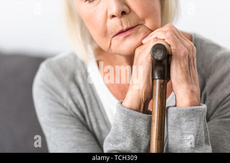 cropped view of pensive senior woman with wooden cane - Stock Photo
