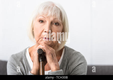 pensive senior woman with wooden cane looking at camera - Stock Photo