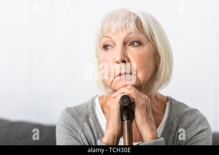 pensive senior woman with wooden cane looking away at home - Stock Photo