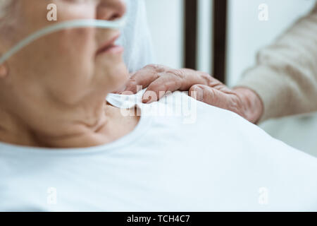 partial view of sick senior woman with husband in hospital - Stock Photo