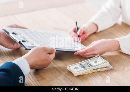 partial view of woman signing contract on clipboard in hands of businessman near dollar banknotes on table - Stock Photo