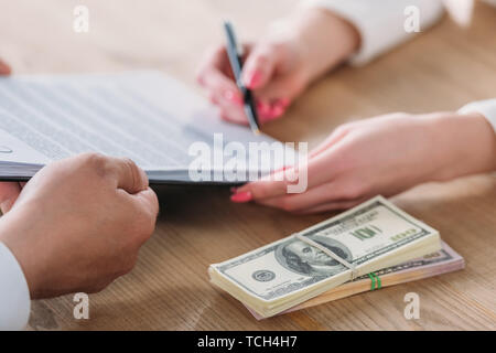 cropped view of woman signing loan agreement on clipboard in hands of businessman near dollar banknotes - Stock Photo