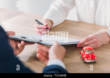 partial view of client signing contract on clipboard in managers hands - Stock Photo