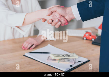 partial view of woman shaking hands with businessman near dollar banknotes on table - Stock Photo