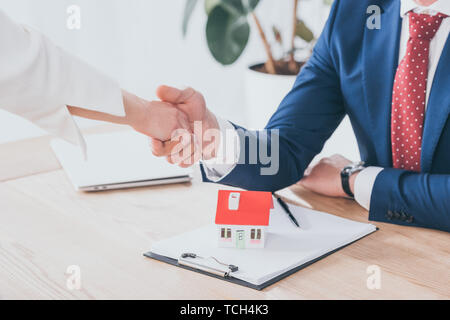 partial view of businessman and client shaking hands near house model on table - Stock Photo