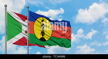 Burundi and New Caledonia flag waving in the wind against white cloudy blue sky together. Diplomacy concept, international relations. - Stock Photo
