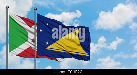 Burundi and Tokelau flag waving in the wind against white cloudy blue sky together. Diplomacy concept, international relations. - Stock Photo