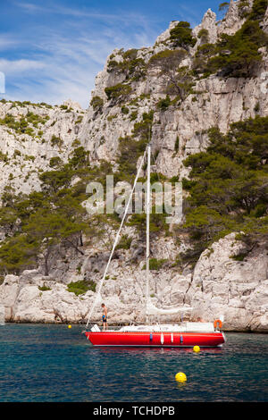 Red sailboat moored in one of the Calanques near Cassis, Provence France - Stock Photo