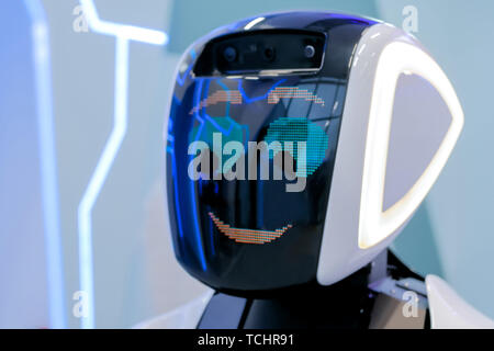 White shy robot with display face at robotic show
