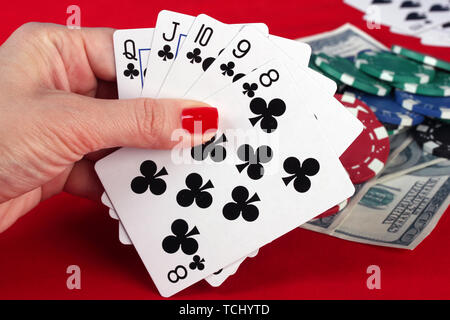 Woman's hand holding playing cards straight flush - Stock Photo