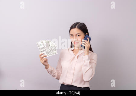 Asian beautiful woman holding banknote money in hand and mobile phone in another hand isolated on grey background. commercial business by phone concep - Stock Photo