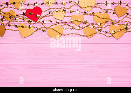 Flat lay border of red and gold hearts of confetti. Golden beads in the form of stars. Festive decor on a pink wooden background. View from above - Stock Photo