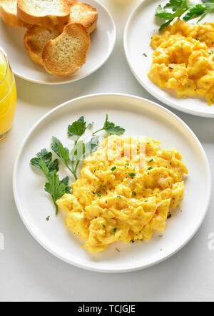 Scrambled eggs on plate over white stone table. Diet dish for breakfast or lunch. - Stock Photo