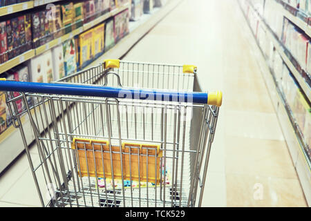 Empty shopping trolley cart in shopping mall interior background. Toy store, Bookstore, household and household goods - Stock Photo