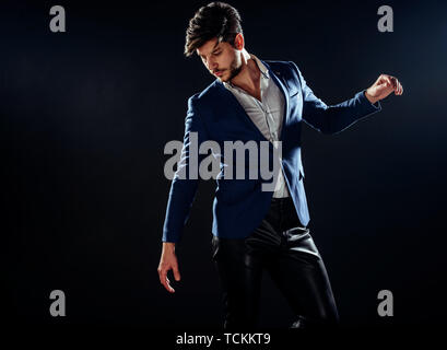 Portrait of serious stylish man in black and blue  outfit looking away - Stock Photo