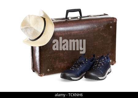 old brown fiber suitcase with hat and sneakers isolated on white background - Stock Photo