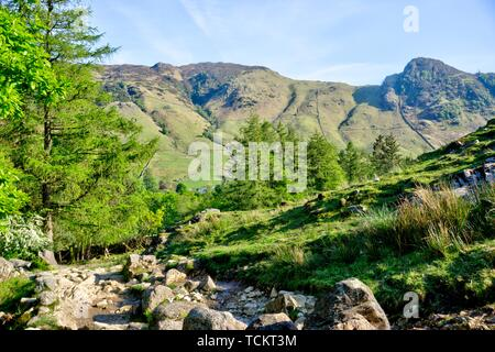 View of Langdale in English Lake District in United Kingdom in evening sunshine with dry stone wall and rocky path in foreground
