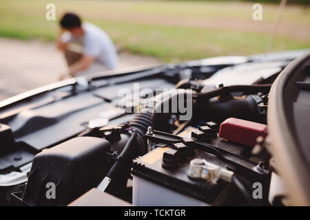 A young man in despair clutched his head, because his car broke down on the road and it is not possible to repair it. - Stock Photo