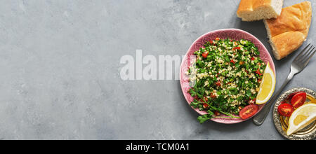 Traditional Middle Eastern and Arabic Tabbouleh salad on gray concrete background, banner. Top view, copy space - Stock Photo