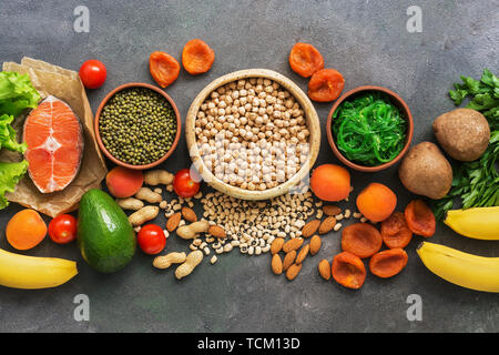 A set of foods high in potassium in a row on a dark background. Healthy balanced meal. Top view, flat lay - Stock Photo