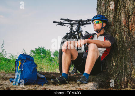 male mountain biker resting on bike ride, sitting on ground under a tree with his mountain bike, stands next to him, enjoying the beautiful nature aro - Stock Photo