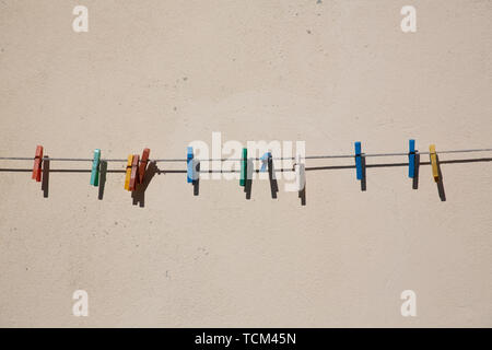 Simple array of colourful clothes pegs or clothes pins on washing line - Stock Photo
