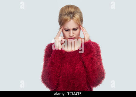 Headache, sadness, confusion or concentration. Portrait of worry alone beautiful young blond woman in red blouse standing, holding painful head. indoo - Stock Photo