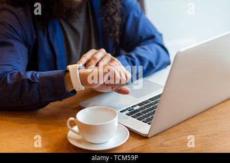 Close up portrait of young adult man freelancer in casual style sitting in cafe with laptop and cup of coffee, looking to the watch to check the time, - Stock Photo