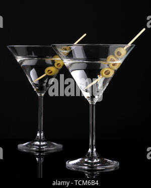 Martini glasses and olives isolated on black - Stock Photo