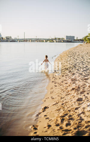 Theme summer outdoor activities near the river on the city beach in Kiev Ukraine. Little funny baby boy running along the river bank, jumping a splash - Stock Photo